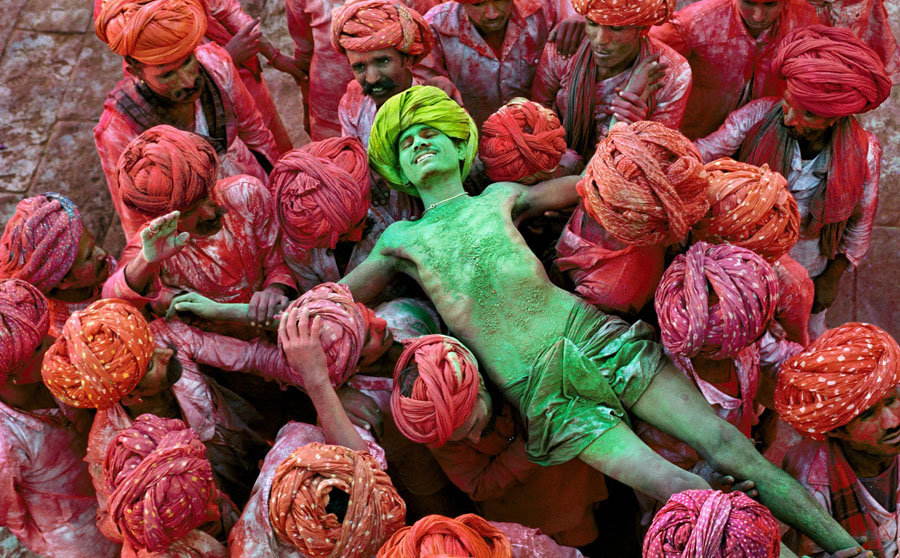 Steve McCurry Rajathan/1996 Crowd carries man during the Holi festival